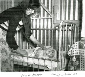 עולה מטריפולי ותינוקה בצריף המעברה בירוחם, 1951