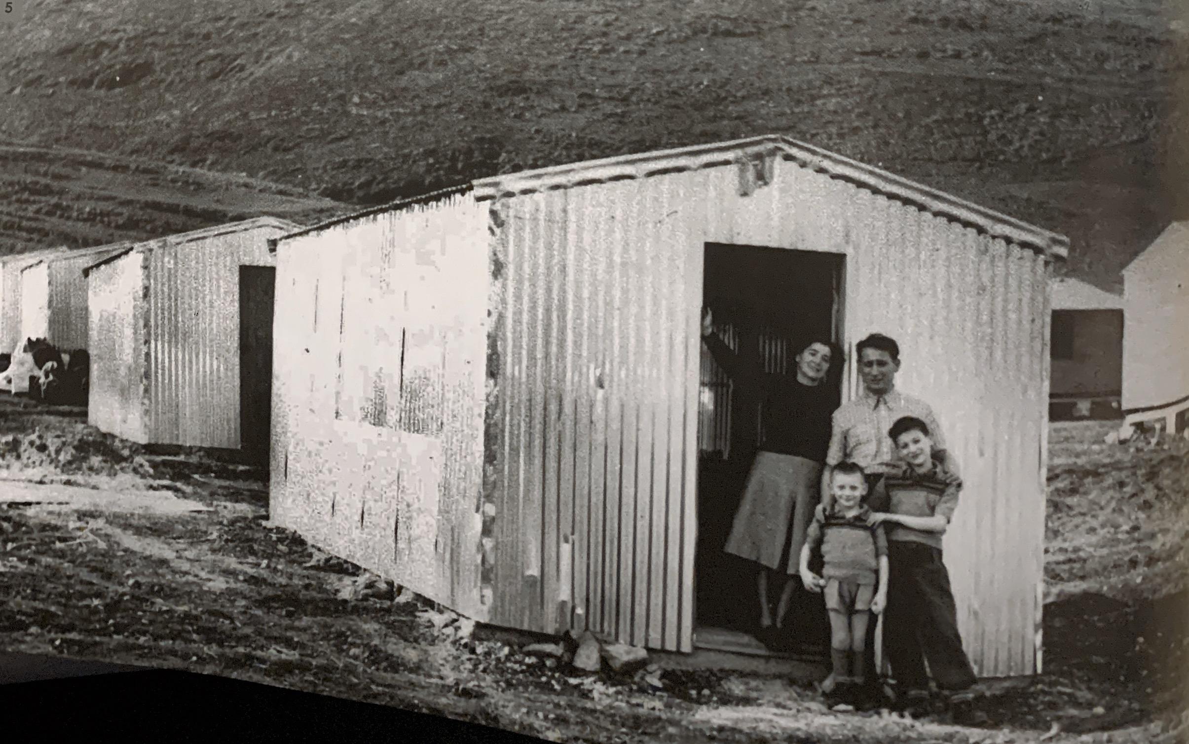 משפחת גרינברג מנתניה בפתח צריפם. מעברת חלסה פברואר 1951